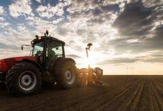 Granjero con el sembrador del tractor - la siembra cosecha en el campo agrícola imágenes de archivo libres de regalías