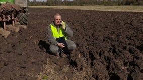 Granjero con la documentación que habla en el teléfono elegante cerca del tractor metrajes