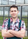 Granjero con los brazos cruzados delante de su invernadero foto de archivo libre de regalías