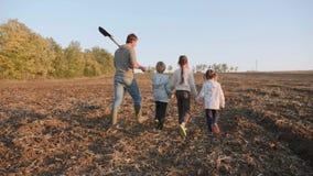 Granjero con sus cuatro niños que van en el campo de granja para el trabajo junto metrajes