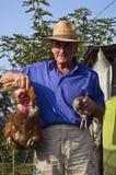 Granjero con un pollo y una codorniz Imagenes de archivo