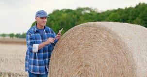 Granjero de la agricultura que trabaja en campo en la tableta digital almacen de metraje de vídeo