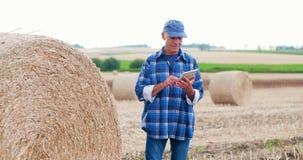 Granjero de la agricultura que trabaja en campo en la tableta digital metrajes