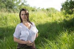 Granjero de la mujer en un campo entre hierba verde Imagenes de archivo