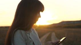 Granjero de la mujer que trabaja con una tableta en campo en sol la mano de la muchacha imprime un mensaje móvil en la pantalla d almacen de video