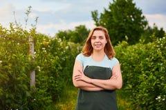 Granjero de la mujer que trabaja en jardín de la fruta El inspector del biólogo examina arbustos de zarzamora imágenes de archivo libres de regalías
