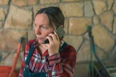 Granjero de sexo femenino preocupante que habla en el teléfono móvil fotos de archivo
