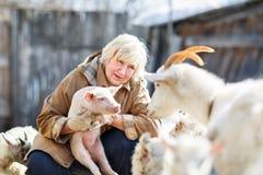 Granjero de sexo femenino que sostiene un pequeño cerdo Imagenes de archivo