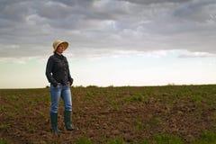 Granjero de sexo femenino Standing en suelo agrícola fértil de la tierra de cultivo Fotos de archivo