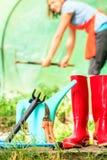 Granjero de sexo femenino y herramientas que cultivan un huerto en jardín Fotografía de archivo libre de regalías