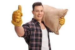 Granjero de sexo masculino que sostiene el saco de la arpillera y que da el pulgar para arriba Fotos de archivo libres de regalías