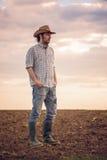 Granjero de sexo masculino Standing en suelo agrícola fértil de la tierra de cultivo Fotos de archivo