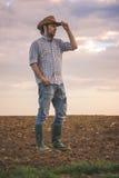 Granjero de sexo masculino Standing en suelo agrícola fértil de la tierra de cultivo Imagen de archivo libre de regalías