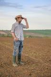 Granjero de sexo masculino Standing en suelo agrícola fértil de la tierra de cultivo Foto de archivo libre de regalías