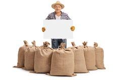 Granjero detrás de los sacos y de sostener de la arpillera el letrero en blanco Foto de archivo libre de regalías