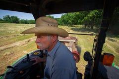Granjero en el tractor que hace heno el campo Imagen de archivo libre de regalías
