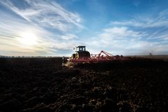 Granjero en el tractor que prepara la tierra con el cultivador del semillero Fotografía de archivo
