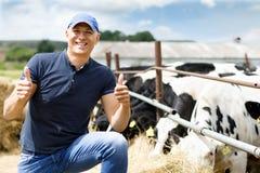 Granjero en la granja con las vacas lecheras imágenes de archivo libres de regalías