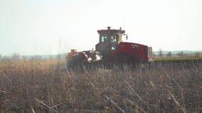 Granjero en la tierra preparada de tierra del suelo de la agricultura de Rusia del tractor con el cultivador del semillero como p metrajes