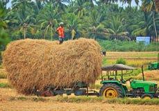 Granjero feliz con el heno y su tractor Imagenes de archivo