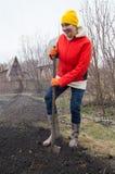 Granjero feliz de la mujer joven que cava con una pala en su jardín Imagen de archivo