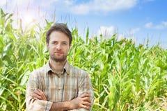 Granjero feliz delante de su campo de maíz Imágenes de archivo libres de regalías