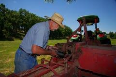 Granjero Greases His Hay Baler Imagenes de archivo