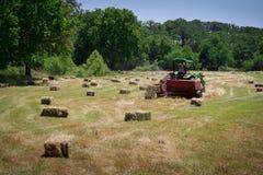 Granjero Haying Field Foto de archivo libre de regalías