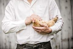 Granjero Holding un pollo beige Imagen de archivo