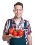 Granjero joven con los tomates frescos Imagenes de archivo