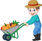 Granjero joven de la historieta que empuja una carretilla por completo de verduras stock de ilustración