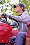 Granjero joven que conduce su tractor Imagen de archivo libre de regalías