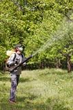 Granjero joven que rocía los árboles con las sustancias químicas foto de archivo