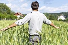 Granjero joven que se coloca en el campo de trigo foto de archivo