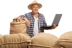 Granjero maduro que presenta con la pila de sacos y de ordenador portátil de la arpillera Imagenes de archivo