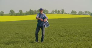 Granjero maduro sonriente Examining Agricultural Field almacen de video