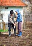 Granjero mayor con el nieto en el jardín Fotografía de archivo libre de regalías