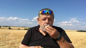 Granjero mayor que come el pepino y el huevo hervido metrajes