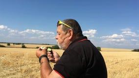 Granjero mayor que come el pepino y el huevo hervido mientras que se sienta al aire libre contra campo de trigo y el cielo azul c metrajes