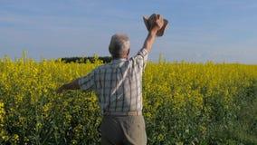 Granjero mayor y blanco-cabelludo en un campo, agitando sus brazos y sombrero en el saludo metrajes