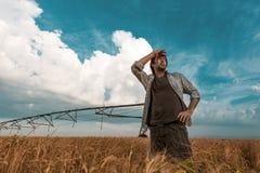 Granjero preocupante en campo de la cebada en un día ventoso foto de archivo