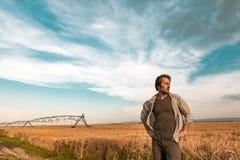 Granjero preocupante en campo de la cebada en un día ventoso imagen de archivo