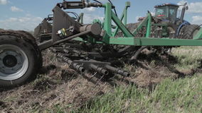 Granjero que ara el campo Pequeña escala que cultiva con el tractor y la paleta en el campo, cultivando el tractor en el campo Gr almacen de video