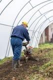 Granjero que ara el suelo en invernadero Fotos de archivo