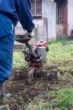 Granjero que ara el suelo en invernadero Fotografía de archivo libre de regalías