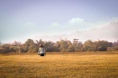 Granjero que camina después de trabajo en un campo de trigo Fotografía de archivo libre de regalías