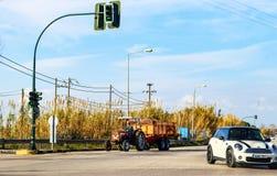 Granjero que conduce el tractor rojo y la carretera grande del remolque abajo en la península septentrional de Peloponeso en Grec Fotos de archivo libres de regalías
