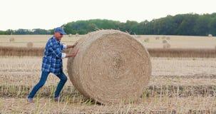 Granjero que lucha mientras que rueda la bala de heno en la granja metrajes