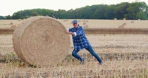 Granjero que lucha mientras que rueda la bala de heno en la granja almacen de video