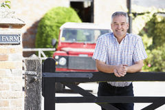 Granjero que mira sobre la puerta de la granja Foto de archivo libre de regalías